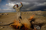 Private Michael Newton of the 82nd Airborne, 1/508 Parachute Infantry Regiment, Alpha Company, Third Platoon jumps over a burning trash pile while waiting for a helicopter flight at Forward Operations Base Diablo in Kandahar province on Saturday, March 31, 2007.