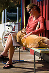 A young woman and her dog relax on a bench in downtown Jackson, Wyoming.