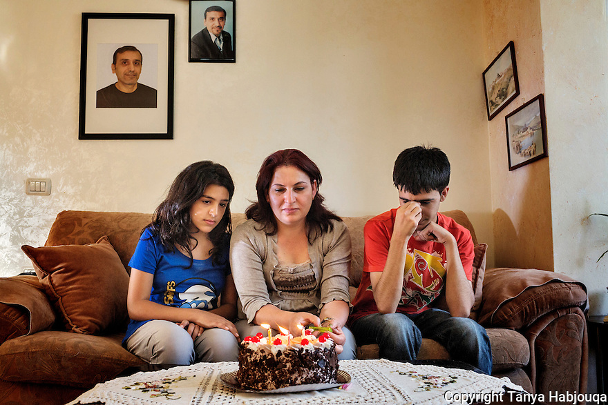 Under the portrait of their imprisoned father, a mother and her two children celebrate another birthday in his absence. west bank