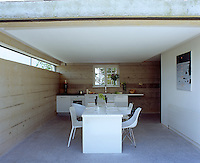 View of the minimal kitchen-diner from outside looking in, with concrete flooring and walls made of concrete