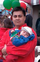 Man age 35 with baby at Cinco de Mayo Festival.  St Paul  Minnesota USA