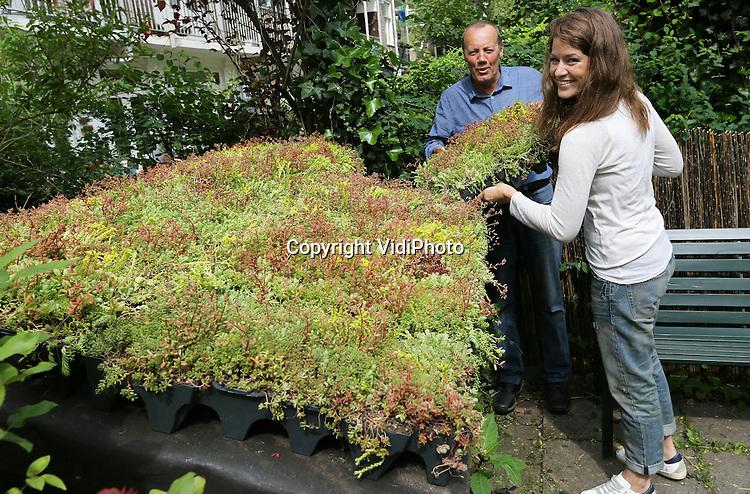 Foto: VidiPhoto<br /> <br /> AMSTERDAM - Tv-corifee Merel Westrik en stadsecoloog Martin Melchers plaatsen woensdag in Amsterdam Mobiroof sedumcassettes op een klein tuinhuisje in Amsterdam. De eco-daken van Mobiroof isoleren en geven de tuin tevens een groener uiterlijk. Het tuinhuisje dient tevens als logeeradres voor dieren in nood. Het Mobiroof-systeem van Mobilane is simpel zelf te leggen en met name geschikt voor platte daken. De Mobiroof-cassettes zijn begroeid met vier tot zes verschillende soorten sedum. Deze plantenmix zorgt voor mooie kleuren gedurende het hele jaar.