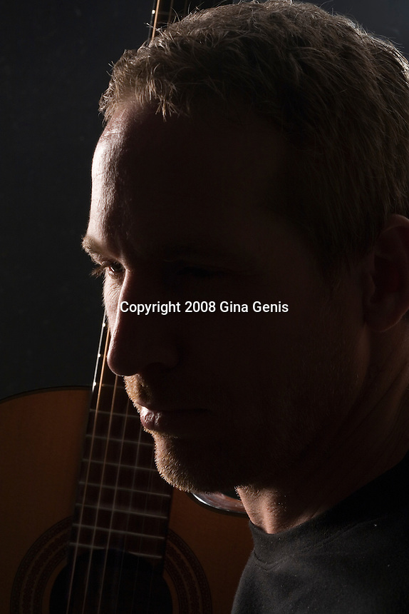 Close up portrait of a man with a classical guitar in backlit studio