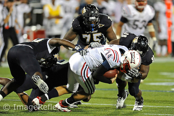 12 November 2011:  FIU defensive tackle Jerrico Lee (98) joins linebacker Kenneth Dillard (41), and defensive end Tourek Williams (97) to sack quarterback Graham Wilbert (14) in the third quarter as the FIU Golden Panthers defeated the Florida Atlantic University Owls, 41-7, to win the annual Shula Bowl game, at FIU Stadium in Miami, Florida.