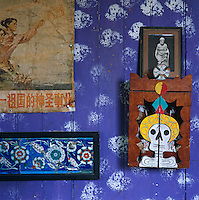 A Chinese propaganda poster, Iznik tiles and a Mexican votive box hang on the wall of the bathrooom