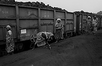 Lady labourers cleaning and accumilating coals at the railway siding in Bailbandh colliery. Generally all the women employees gets the job as dependents of deceased workers. Kunostoria coal field in Ranigunj, West Bengal, India. Arindam Mukherjee