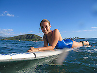 A young woman takes a break from surfing at Rest Camp, or Pilila'au Army Recreation Center, Poka'i Bay, West O'ahu.