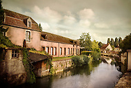 Aged buildings sit on a beautiful canal that runs through the French city La Ferté Benard