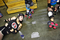 Harlot Fevah stretches before a roller derby practice in Wilmington, Massachusetts. Roller derby is an American contact sport, popular with young women, which combines both athleticism and a satirical punk third-wave feminism aesthetic.