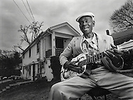 African-american blues musician, John Dee Holeman, laughs as he plays his guitar in front of his home in Durham, North Carolina.