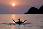 Person enjoys the peace and serenity of a Lanikai sunrise while practicing shibashi in the water. Morning sun is a fireball from the volcanic fog (VOG).