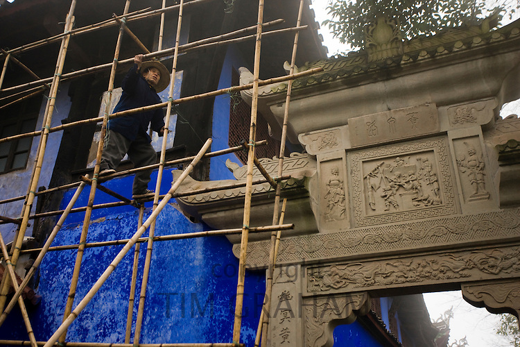 Workman carries out restoration repairs at City of Ghosts, Fengdu, China