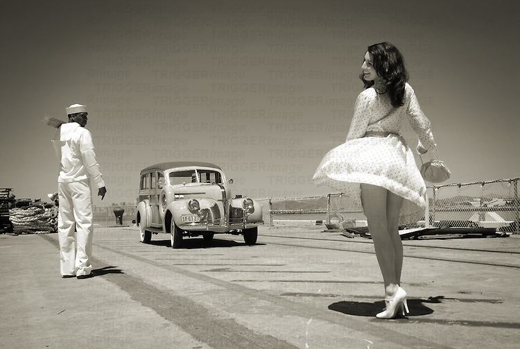 A model wearing a short white dress near a sailor and vintage car