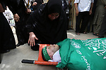 Relatives of Palestinian Mohammed Alian, 20, who died of wounds he sustained during clashes with Israeli troops in a tent city protest where Palestinians demand the right to return to their homeland and against U.S. embassy move to Jerusalem at the Israel-Gaza border, mourn over his body during his funeral in Nusseirat refugee camp in the Gaza Strip on May 19, 2018. Photo by Ashraf Amra