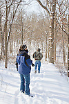 Photographers walk in the snow in the woods on a cold winter day.