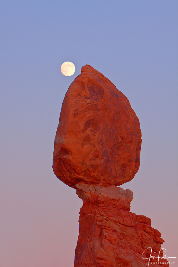 Telephoto image of the rising full moon behind Balanced Rock in Arches National Park, near Moab, Utah, at sunset.