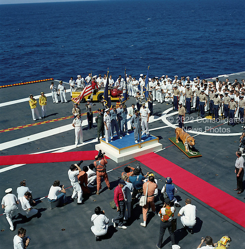 "Pacific Ocean - (FILE) -- A high-angle view is of the Apollo 16 welcoming aboard ceremonies on the deck of the prime recovery ship, U.S.S. Ticonderoga that took place after splashdown of the command module in the central Pacific Ocean approximately 215 miles southeast of Christmas Island. Mission commander John Young stands at the microphone. Standing behind him are lunar module pilot Charles Duke and command module pilot Thomas Mattingly. The splashdown occurred at 1:45 p.m. CST Thursday, April 27, 1972.  This photo is part of the book ""Apollo: Through the Eyes of the Astronauts"" published to commemorate the 40th anniversary of the first manned lunar landing on July 20, 1969..Credit: NASA via CNP"