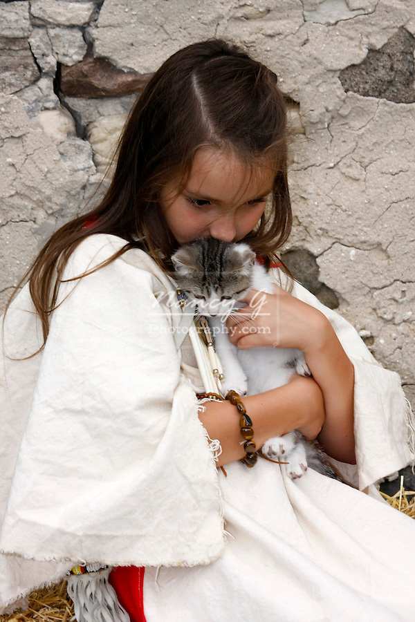 A Native American Indian girl hugging a kitten