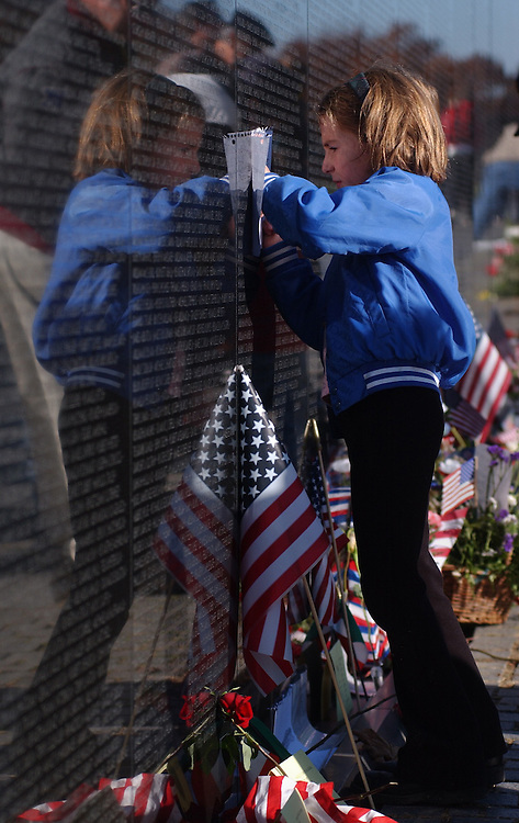 2veterans111201 -- On Veterans Day at the Wall, Alexis Maxwell, 7, whose father is stationed at Quantico, Va., makes a rubbing of her grandfather's cousin, killed in Vietnam.