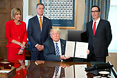 United States President Donald J. Trump holds up the order after signing the second of three Executive Orders concerning financial services at the Department of the Treasury in Washington, DC on April 21, 2017.  From left to right: US Representative Claudia Tenney (Republican of New York) US Senator David Perdue (Republican of Georgia), the President, and US Secretary of the Treasury Steven Mnuchin.<br /> Credit: Ron Sachs / Pool via CNP