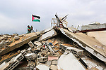 Palestinian boy hang the flag on the rubble of their destroyed house on a winter cold day, in Khan Youns southern in Gaza city January 20, 2020. Photo by Ashraf Amra