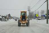 Loader  driving along city street in winter