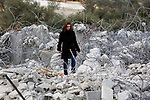 A Palestinian girl walks on the rubble of two under-construction Palestinian residential buildings after they were demolished by Israeli bulldozers in the West Bank town of Biet Jala, near Bethlehem January 29, 2018. Photo by Wisam Hashlamoun
