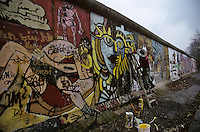 French artist Thierry Noir retouches his graffitti on a section of the Berlin Wall