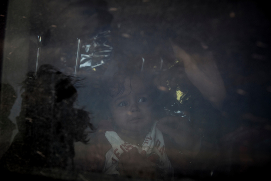 October 31, a boy looks out of the window of a transport van. Volunteers oftentimes drive immigrants from their landing sites. Boats often land several kilometers or more from the nearest village or camp.