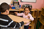Preschool 4-5 year olds block area children playing with wooden blocks boy and girl working together girl watching boy set block in place placing flat block on top excited happy horizontal