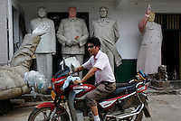 "A man rides past unfinished statues of Mao Zedong at the workshop of a ""Red"" memorabilia collector and manufacturer, near Mao's birthplace in Shaoshan, Hunan Province, China on 12 August 2009."