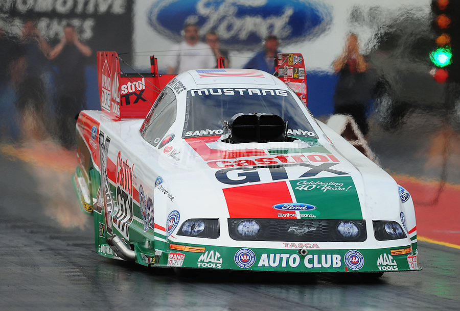Jan 23, 2009; Chandler, AZ, USA; NHRA funny car driver John Force launches off the starting line during testing at the National Time Trials at Firebird International Raceway. Mandatory Credit: Mark J. Rebilas-
