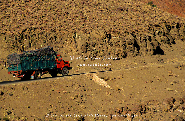 Truck carrying a heavy load drives through the mountainous desert, Telouet, Morocco.