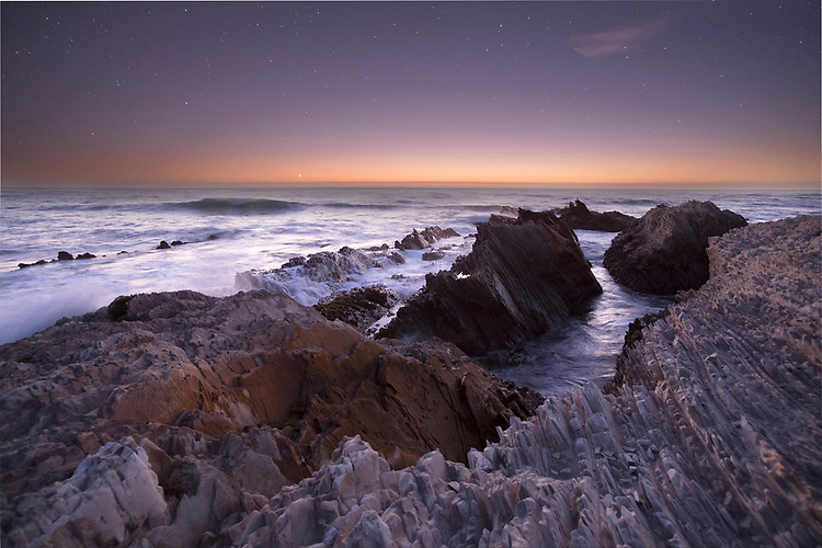 The last glow of dusk on the ocean's horizon softly illuminates the ragged, vertical rock strata on the sea cliffs of Montana de Oro state park.