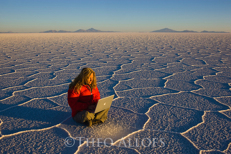 Bolivia, Altiplano, Salar de Uyuni, world's largest salt pan; woman sitting on hexagons working with laptop at sunrise --- Model Released