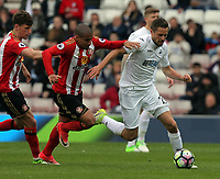 SUNDERLAND, ENGLAND - MAY 13: Gylfi Sigurdsson of Swansea City (R) is fouled by Wahbi Khazri of Sunderland (C)   during the Premier League match between Sunderland and Swansea City at the Stadium of Light, Sunderland, England, UK. Saturday 13 May 2017
