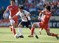 USA's Lee Nguyen dribbles the ball between China's Zhao Xuri (21) and Zhang Yaokun (4). The USA defeated China, 4-1, in an international friendly at Spartan Stadium, San Jose, CA on June 2, 2007.
