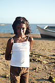 MAURITIUS, a young girl walks on the beach by a fishing boat in Bel Ombre