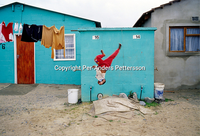township,poverty,children,kids,laundry,water tap,.Children play outside a house on June 17, 2004 in Khayelitsha, the biggest black township, about 20 miles outside Cape Town, South Africa. .©Per-Anders Pettersson/iAfrika Photos.......