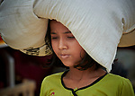 A Rohingya girl carries food supplies she received from Dan Church Aid in the Jamtoli Refugee Camp near Cox's Bazar, Bangladesh. Dan Church Aid is a member of the ACT Alliance.<br /> <br /> More than 600,000 Rohingya have fled government-sanctioned violence in Myanmar for safety in Bangladesh.