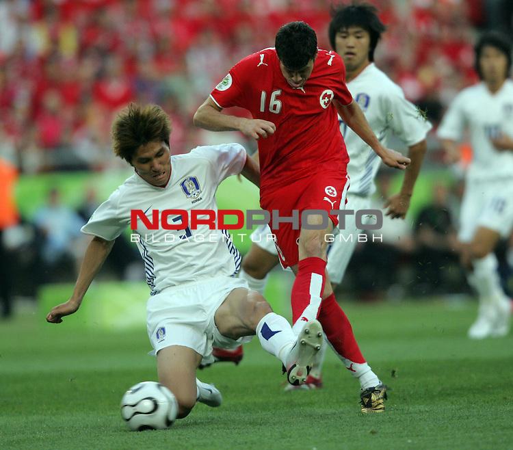 FIFA WM 2006 -  Gruppe G  Vorrunde ( Group G )<br /> Play    #46 (23-Jun) - Schweiz - S&uuml;dkorea<br /> <br /> Tranquillo Barnetta (rechts) von der Schweiz beim Torschuss Versuch. Dong Jin Kim (links) von Korea versucht ihn daran zu hindern.<br /> <br /> Foto &copy; nordphoto