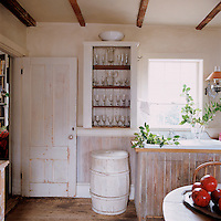 A rustic cupboard on the kitchen wall has had its door removed and is used to store glassware