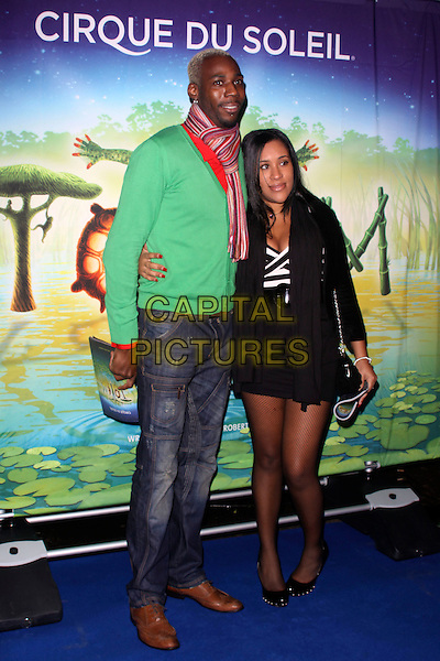 "PHILLIPS IDOWU & GUEST.The Cirque du Soleil ""Totem"" press Tour, Royal Albert Hall, Kensignton Gore, London, England..January 5th, 2011.full length jumper sweater jeans denim  black green stripe scarf facial hair red.CAP/AH.©Adam Houghton/Capital Pictures."