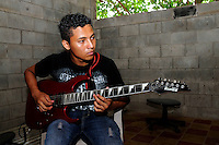 A member of the group 'Sacreficio' rehearses for a performance, led by music teacher Pedro Esquival Chavez of the Music for Hope youth project based in the community of Zamoran, El Salvador.