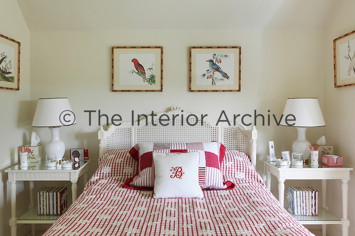 A carved bed with red and white checked bedding and a monogrammed cushion
