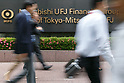 Pedestrians walk past a signboard of Bank of Tokyo-Mitsubishi UFJ on display outside its building on May 17, 2017, Tokyo, Japan. Japan's biggest bank plans to shorten its name by dropping ''Tokyo'' to Bank of Mitsubishi UFJ. (Photo by Rodrigo Reyes Marin/AFLO)