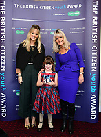 Pictured: Elly Neville with (C) presented The British Citizen Award for the Good of the Country by Kimberly Wyatt (L) and First News newspaper editor Nicky Cox.<br /> Re: Seven-year-old Elly Neville who was born despite doctors saying her parents would not be able to have any more children, has raised over &pound;150,000 for the cancer ward that treated her father.<br /> Her parents Lyn and Ann had been told they were unlikely to have more children after he underwent a bone marrow transplant in 2005. <br /> Mr Neville subsequently spent a lot of time on the Ward 10 cancer facility at Withybush Hospital in Haverfordwest, Pembrokeshire.<br /> But four years later they were stunned when his painter and decorator wife Ann fell pregnant again.