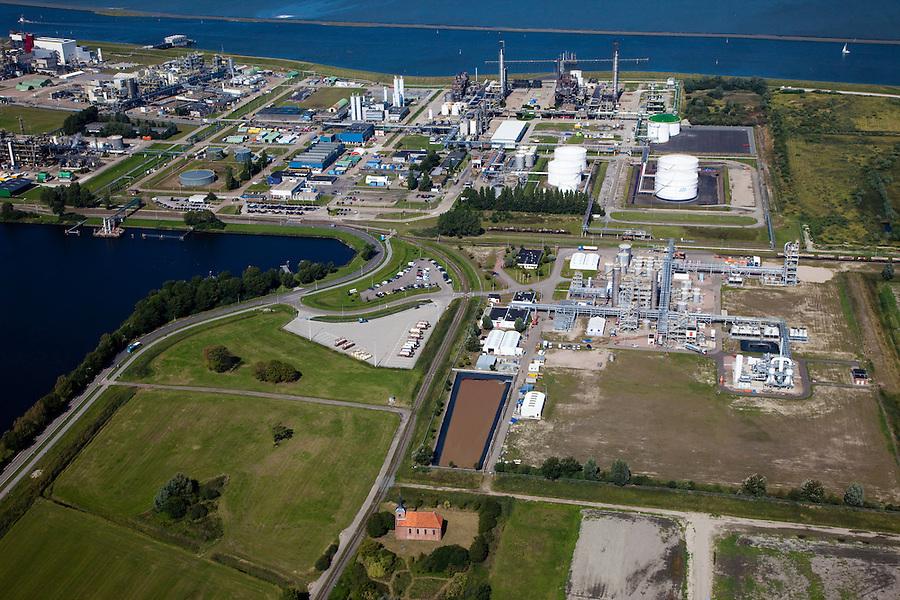 Nederland, Groningen, Delfzijl, 08-09-2009; Industrieterrein Eemsmondgebied met Chemie park. Het kerkje met dak van rode pannen is dat van het verdwenen dorpje Heveskes dat in het verleden ruimte moet maken voor het industrieterrein. Chemiepark.nl  huisvest onder andere AkzoNobel (soda, chloor, zout)..Industrial Estate of the Eemsmond area with aluminum smelter Aldel (aluminum Delfzijl) right, to the left part of the Chemical Park. The little church with red roof tiles belongs to the village Heveskes, the village had to make room for the for the industrial park in the past Chemiepark.nl houses  Akzo Nobel (soda, chlorine, salt).luchtfoto (toeslag); aerial photo (additional fee required); .foto/photo Siebe Swart