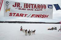 Marianna Mallory runs under the finish line banner of the 2016 Junior Iditarod in Willow, Alaska, AK  February 28, 2016