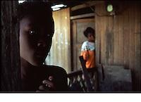 primo piano di ragazzo di colore, donna guarda dalla porta della capanna nel villaggio di Buenavista, monitorato dall'OMS per malaria<br /> gros plan d'un jeun noir, avec une femme qui regarde par la porte de la cabane dans le village de Buenavista, suivis par l'OMS pour le paludisme<br /> close-up of a young black, woman looks out the door of the hut in the village of Buenavista, monitored by WHO for malaria